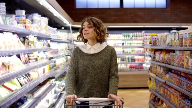 Portrait of happy, relaxful woman with curly hair went shopping with trolley cart - walk by a row and happily dancing in relaxful mood. Slow motion Portrait of happy, relaxful woman with curly hair went shopping with trolley cart - walk by a row and happily dancing in relaxful mood. Slow motion. woman pushing cart stock videos & royalty-free footage