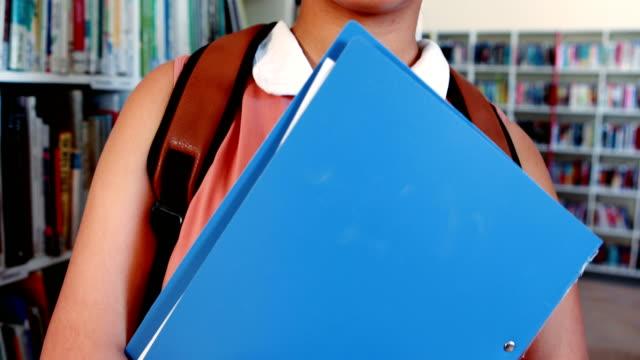 Portrait of happy schoolgirl standing in library video
