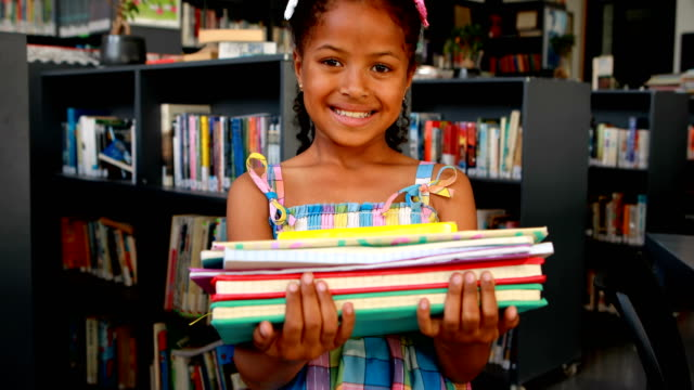 Portrait of happy schoolgirl standing with book stack 4k video