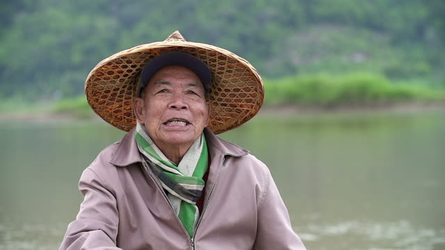 portrait of happy senior asian fisherman with a smiley face sitting near the river. - индонезия стоковые видео и кадры b-roll