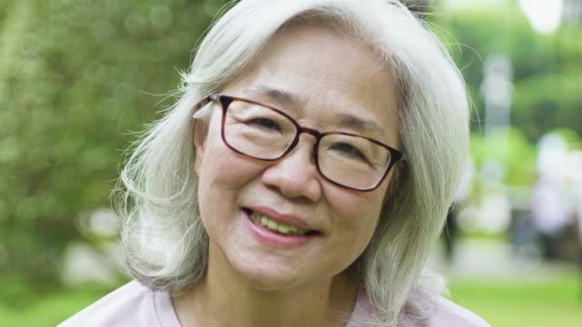公園裡快樂的亞洲老婦人的肖像 - 亞太地區 個影片檔及 b 捲影像