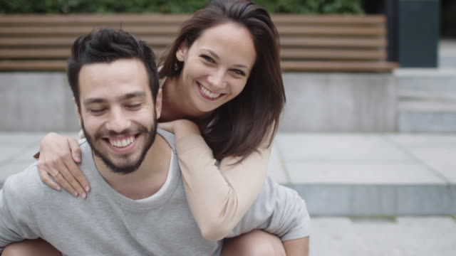 portrait of happy smiling couple outdoors. young woman hugging the man - couple portrait caucasian video stock e b–roll
