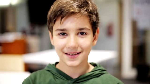 portrait of happy smiling preteen boy face at school classroom - children video stock e b–roll