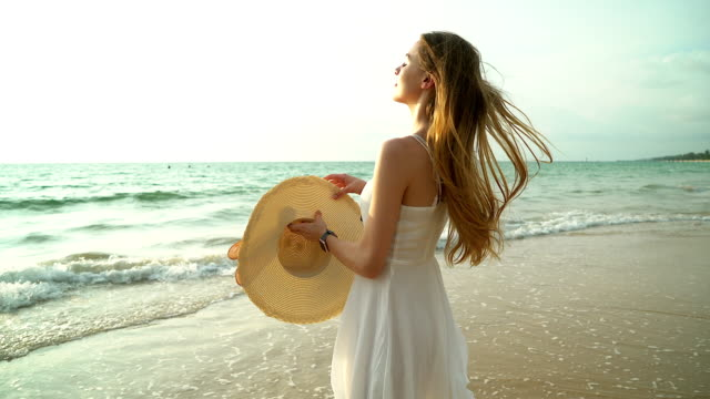 Portrait of happy smiling woman on the beach. Smiling sensual blonde posing on a beautiful wild beach. Pretty girl in casual looking away during sunset. video