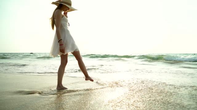 ビーチで幸せな笑顔の女性の肖像画。官能的な金髪の美しい野生のビーチでポーズをとって笑顔。カジュアルな日没時によそ見できれいな女の子。 ビデオ