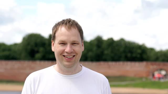 stockvideo's en b-roll-footage met portret van gelukkig lachend jonge man buitenshuis - alleen één mid volwassen man