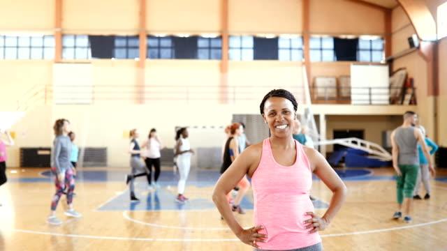 spor salonunda mutlu gülümseyen genç kadın portresi - orta yetişkin stok videoları ve detay görüntü çekimi