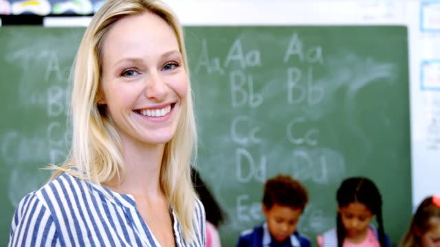 porträt von glücklich lehrer im klassenzimmer - highschool lehrer stock-videos und b-roll-filmmaterial