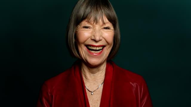 vídeos de stock e filmes b-roll de portrait of happy woman against green background - old lady