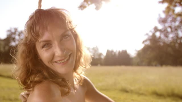 SLO MO Portrait of happy woman on a swing video