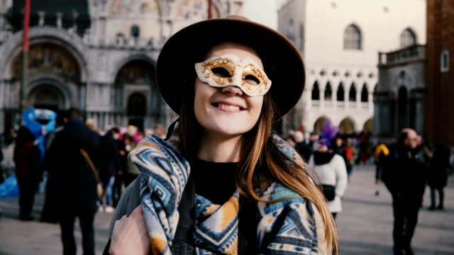 Portrait of happy woman with long hair wearing a white carnival face mask in Venice city square, Italy blowing kisses. Portrait of happy woman with long hair wearing a white carnival face mask in Venice city square, Italy blowing kisses. Cheerful excited female traveler posing, enjoying atmospheric vacation trip. long hair stock videos & royalty-free footage