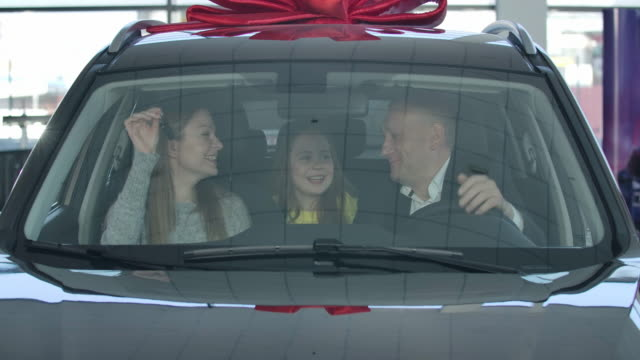 Portrait of happy young Caucasian family sitting in car in dealership. Pretty woman showing keys to husband and daughter. Automobile industry, lifestyle, success. Cinema 4k ProRes HQ.
