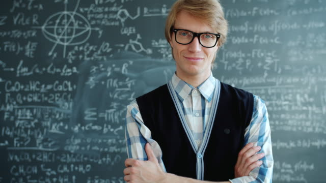 Portrait of happy young man student standing in class smiling looking at camera Portrait of happy young man student standing in class with arms crossed smiling looking at camera. Occupation, lifestyle and modern people concept. genius stock videos & royalty-free footage
