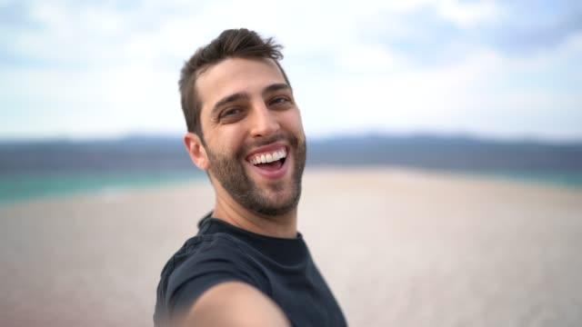 porträt eines glücklichen jungen mannes, der ein selfie am strand macht - selfie stock-videos und b-roll-filmmaterial