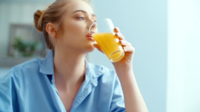 vídeos y material grabado en eventos de stock de retrato de feliz joven bebiendo jugo de naranja durante el desayuno. - zumo