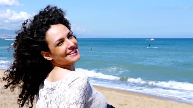 vídeos de stock, filmes e b-roll de retrato de mulher jovem feliz com cabelo encaracolado bonito, desfrutar do sol de verão na costa do mar do - sul europeu