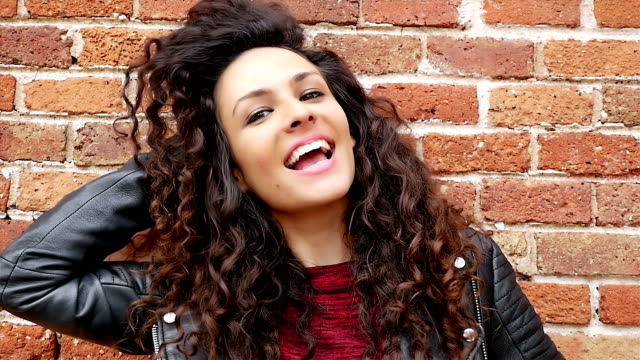 portrait of happy young woman with beautiful curly hair on a brick wall, slow motion - capelli ricci video stock e b–roll