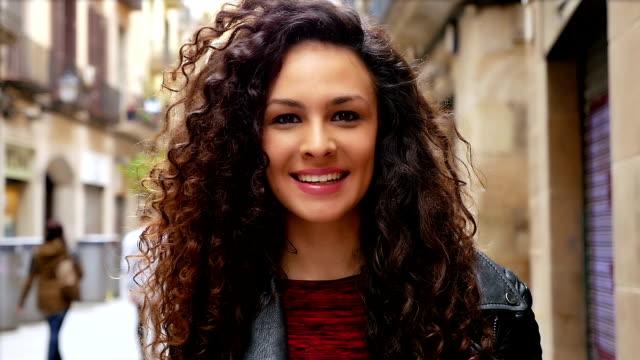 portrait of happy young woman with beautiful curly hair walking in the city, slow motion - brązowe włosy filmów i materiałów b-roll