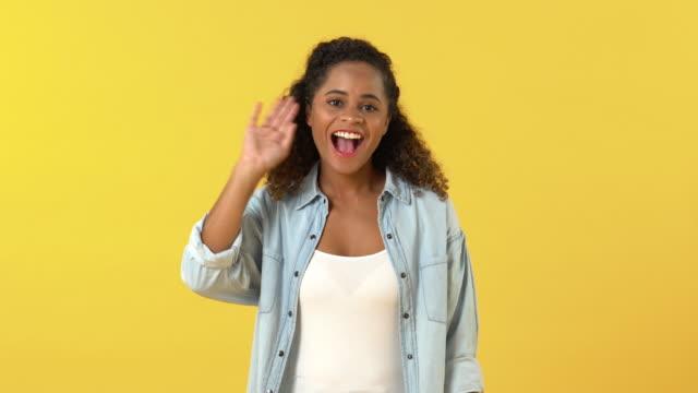 Portrait of happy young woman with curly hair waving Portrait of happy young woman with curly hair waving bye and showing OK sign in front of camera against yellow background goodbye single word stock videos & royalty-free footage