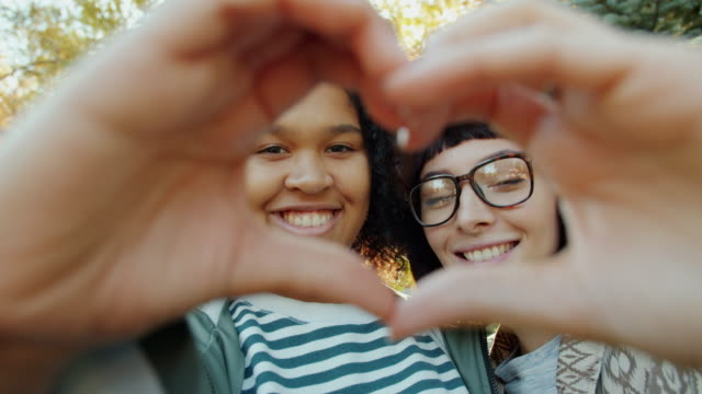 Portrait of happy young women friends showing heart gesture with hands smiling video