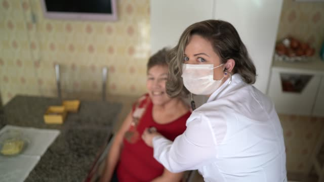 Portrait of health visitor and a senior woman during home visit Portrait of health visitor and a senior woman during home visit cardiologist stock videos & royalty-free footage