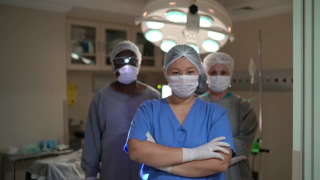 Portrait of healthcare coworkers with face mask on operating room at hospital