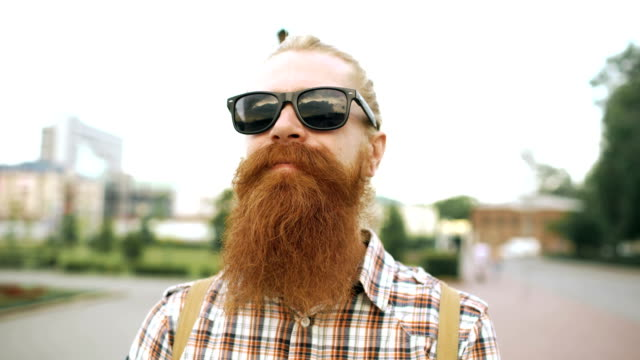 Portrait of hipster bearded tourist man in sunglasses looking at camera and smiling at city background video