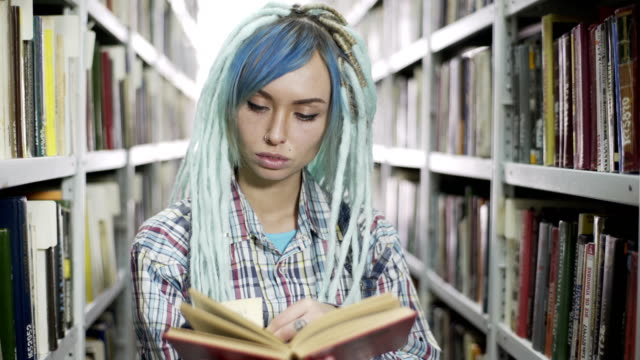 Portrait of hipster woman reading book in library Portrait of a hipster woman reading book in library blue hair stock videos & royalty-free footage