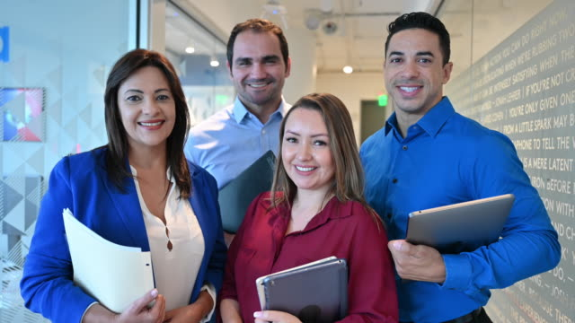 portrait of hispanic business team in hallway - fianco a fianco video stock e b–roll