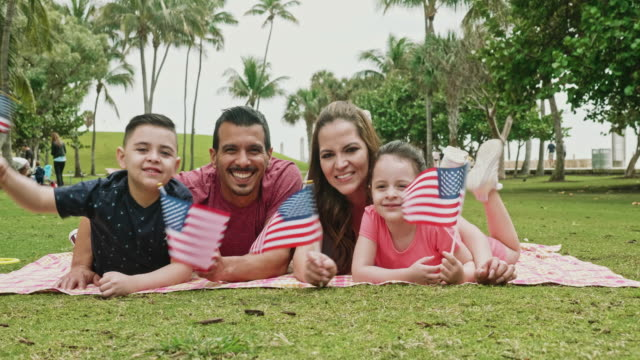 Portrait of Hispanic Family Celebrating American Holiday Smiling Hispanic American parents in late 30s with 4 and 6 year old children holding American flags and celebrating holiday with picnic at Miami park. family 4th of july stock videos & royalty-free footage
