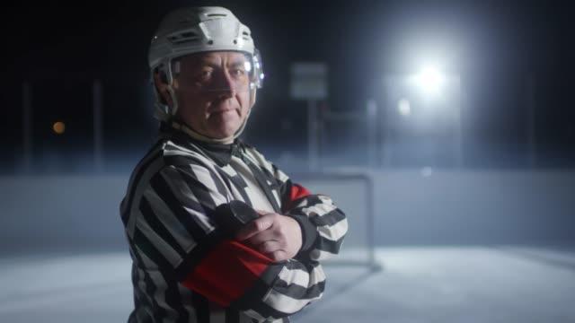 vidéos et rushes de portrait de l'arbitre de hockey retenant la rondelle - hockey sur glace
