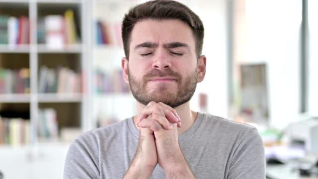 portrait of hopeful young man praying with closed eyes - верующий стоковые видео и кадры b-roll