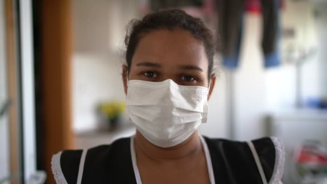 portrait of housekeeper wearing protective mask at house - mask стоковые видео и кадры b-roll