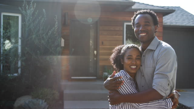 Portrait Of Hugging Couple Standing Outdoors In Front Of House Portrait of hugging couple standing outdoors in front of house against flaring sun - shot in slow motion new home stock videos & royalty-free footage