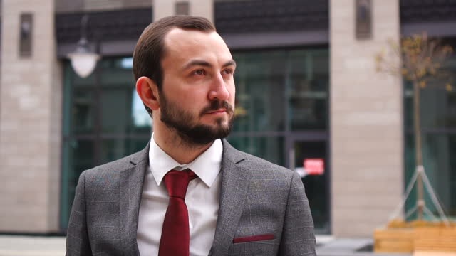 Portrait of independent man looking serious confident in urban background wearing business suit Portrait of independent man looking serious confident in urban background wearing business suit. businesswear stock videos & royalty-free footage
