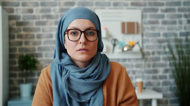 portret niezależnej muzułmańskiej dziewczyny w okularach hidżab patrząc na kamerę w biurze - islam filmów i materiałów b-roll