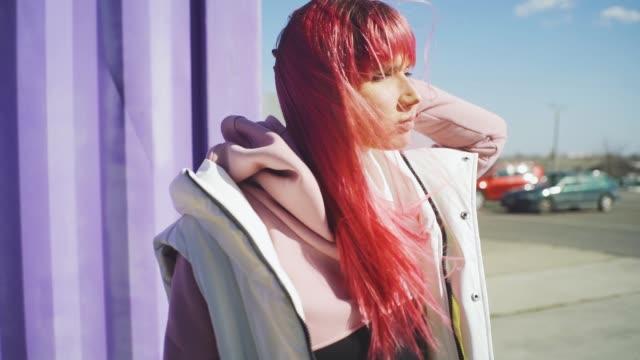 stockvideo's en b-roll-footage met portret van onafhankelijke jonge vrouw met roze haar poseren op paarse containers achtergrond. slow motion - roze haar