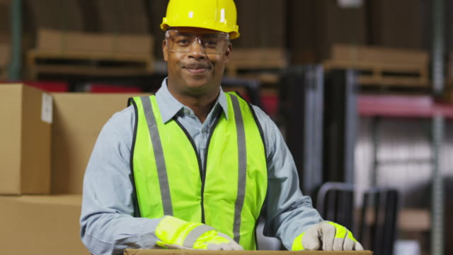 Portrait of industry worker in shipping warehouse video