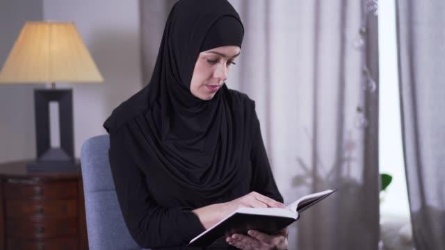 porträtt av intelligent muslimsk kvinna i hijab läsa bok hemma. koncentrerad ung kvinna gör överraskad ansikte och rörande mun. intelligens, hobby, livsstil. - anständig klädsel bildbanksvideor och videomaterial från bakom kulisserna