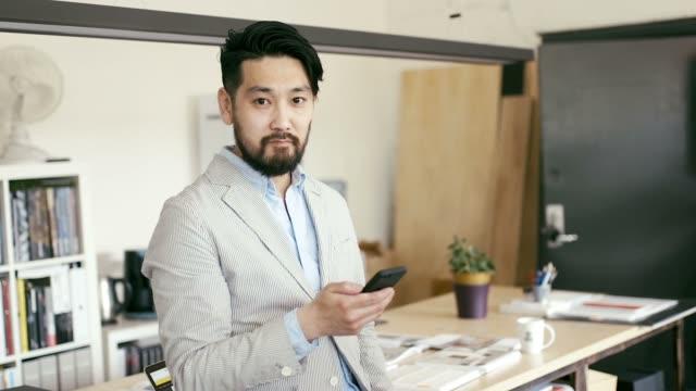 スマート フォンで日本のグラフィック デザイナーの肖像 - スタジオ 日本人点の映像素材/bロール