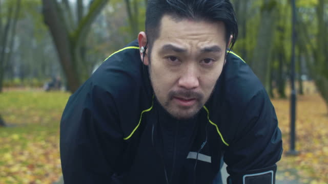 Portrait of Japanese Runner Japanese man runs in the park on a rainy day with smartphone and headphones. exhaustion stock videos & royalty-free footage