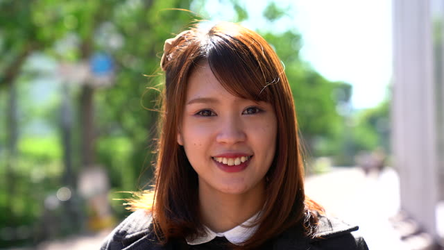 portrait of japanese woman smiling to the camera with city building as background. - primo piano del volto video stock e b–roll