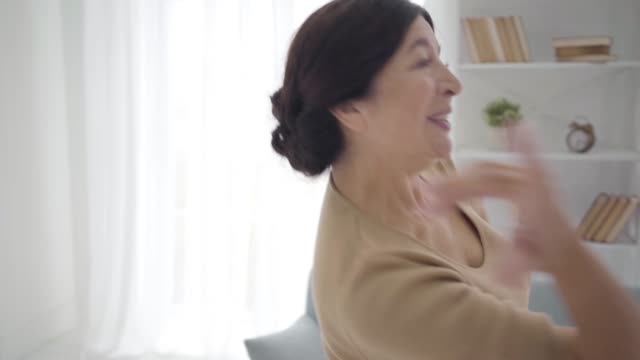 Portrait of joyful Caucasian female retiree enjoying free life at home. Camera moving down from smiling face of happy woman to feet in beige high-heels. Elegant lady having fun. Leisure, happiness.