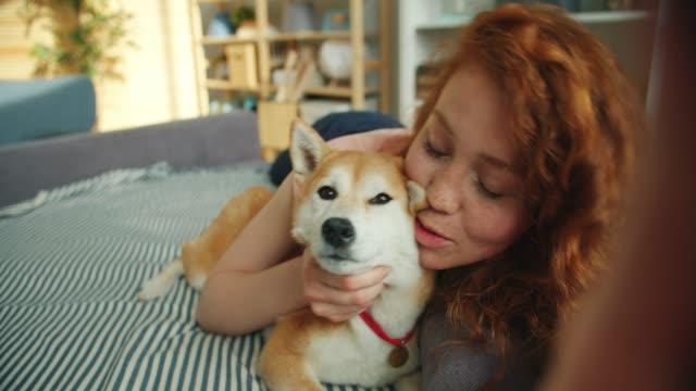 Portrait of joyful girl kissing shiba inu dog and taking selfie holding camera
