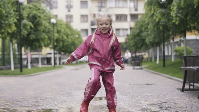 Portrait of joyful little girl having fun playing in puddle on rainy day. Wide shot of cheerful Caucasian blond child resting outdoors. Fun, joy, leisure, childhood. Portrait of joyful little girl having fun playing in puddle on rainy day. Wide shot of cheerful Caucasian blond child resting outdoors. Fun, joy, leisure, childhood. stamping feet stock videos & royalty-free footage