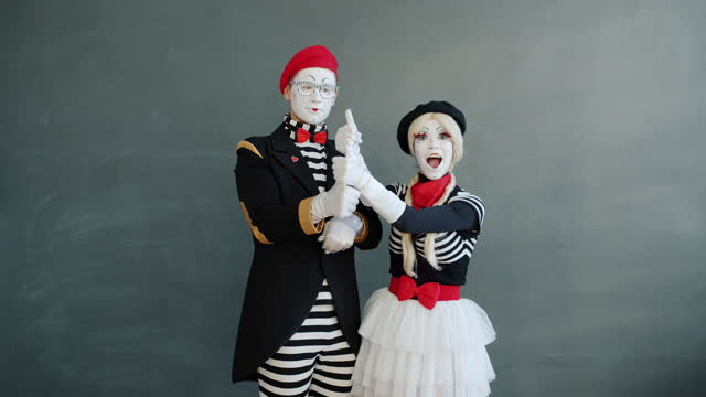 Portrait of joyful mimes guy and girl showing thumbs-up hand gesture smiling