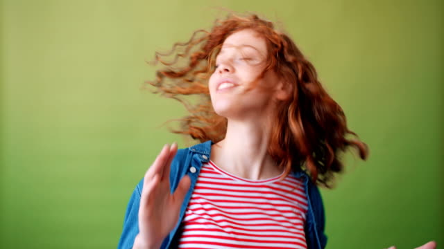 portrait of joyful red-haired girl dancing and smiling on green background - capelli ricci video stock e b–roll