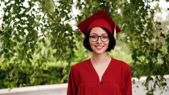 Portrait of joyful young woman graduating student in gown and mortar-board smiling and looking at camera standing under the tree on campus. Youth and education concept. Portrait of joyful young woman graduating student in red gown and mortar-board smiling and looking at camera standing under the tree on campus. Youth and education concept. diploma stock videos & royalty-free footage