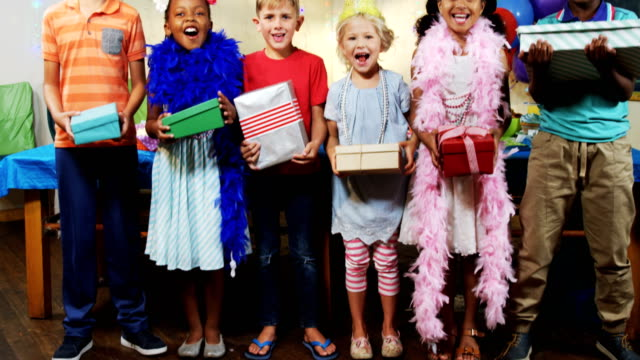 Portrait of kids holding gift boxes during birthday party 4k video