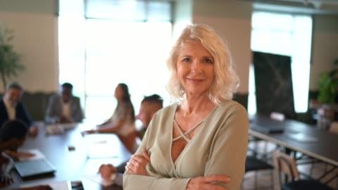 vidéos et rushes de verticale de femme d'affaires mûre de chef à la table de conférence - courage